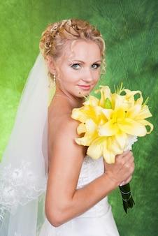 Mariée avec un bouquet de lis jaunes.