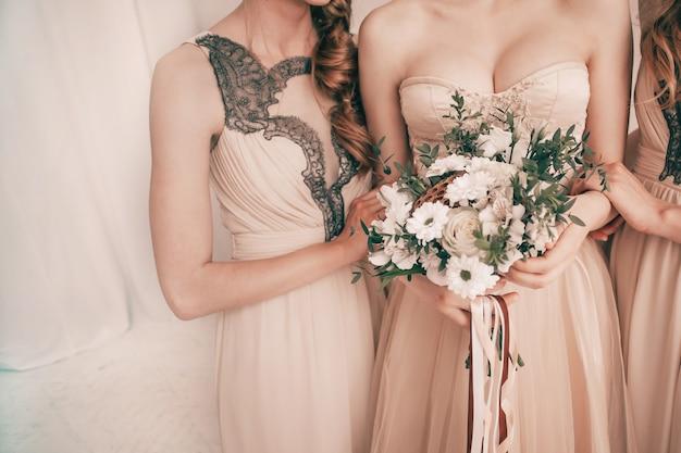 Mariée avec un bouquet de mariage debout avec ses amis.
