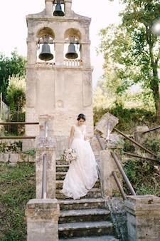 La mariée avec bouquet de mariée debout sur les escaliers de l'ancien clocher près de l'église de