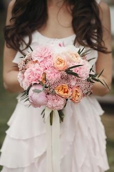 Mariée avec un bouquet de roses roses et des pivoines de luxe