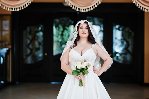 Mariée brune aux gros seins avec bouquet de mariée posée aux rideaux d'arrière-plan de la salle des mariages