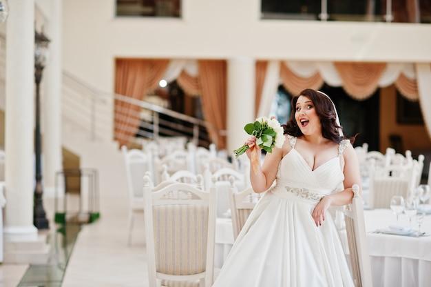 Mariée brune aux gros seins avec bouquet de mariée posée aux tables de la salle du mariage