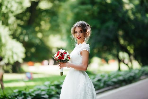 Mariée brune dans une robe avec un bouquet de mariée dans le parc
