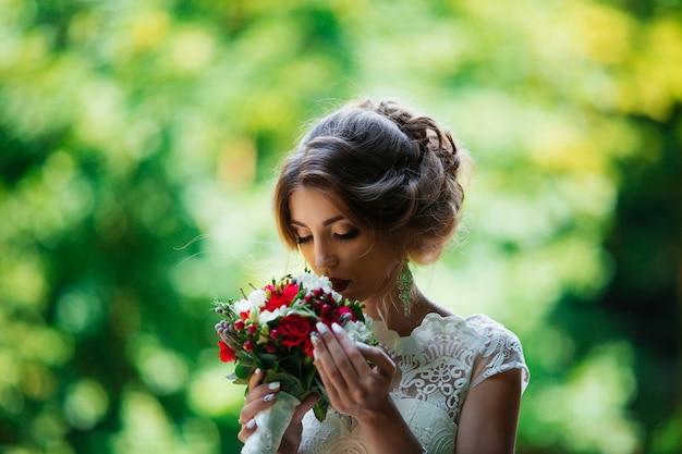 Mariée brune dans une robe de mariée et un bouquet au coucher du soleil dans le parc