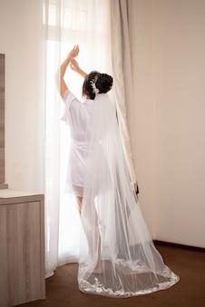 La mariée brune dans un voile et une robe en soie avec une épingle à cheveux dorée dans ses cheveux se tient devant la fenêtre avec des rideaux dans la chambre