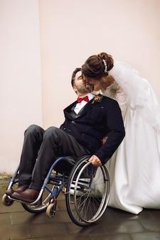 Mariée calins marié sur le fauteuil roulant par derrière posant dans la rue
