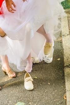 La mariée change de chaussures de sport lors d'une promenade de mariage dans un parc
