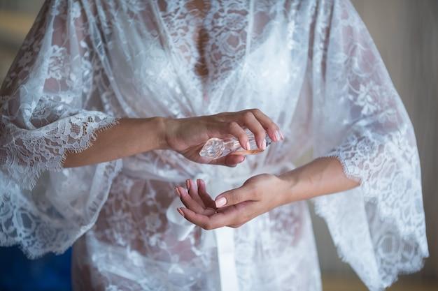 Mariée en chemise boudoir blanche appliquant du parfum sur son poignet