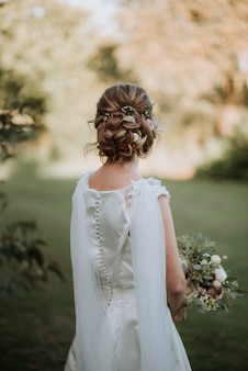 Mariée avec une coiffure de mariée portant une robe de mariée tenant un bouquet de fleurs