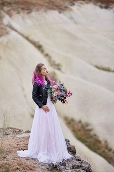 La mariée avec une coloration créative des cheveux regarde au loin dans la nature. portrait d'une femme aux cheveux aux couleurs vives debout dans les montagnes de la cappadoce en turquie. mariage dans la nature