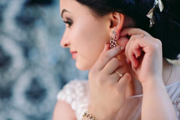 La mariée corrige la boucle d'oreille, belles boucles d'oreilles et mains de la mariée