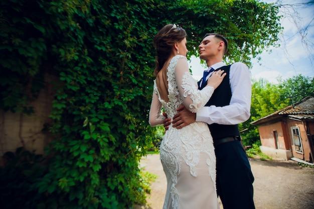 Une mariée avec une coupe courte et un marié élégant se promènent dans le parc.