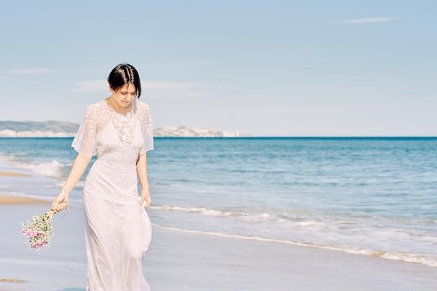 Mariée courir joyeusement le long de la plage dans sa robe de mariée et tenant un bouquet de fleurs à la main