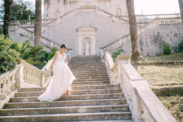 La mariée en couronne descend les escaliers pittoresques de l'ancien temple en vue arrière de prcanj