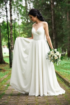 La mariée dans une belle robe blanche et un bouquet de fleurs dans ses mains attend la cérémonie de mariage. belle femme avec un bouquet de mariage dans ses mains