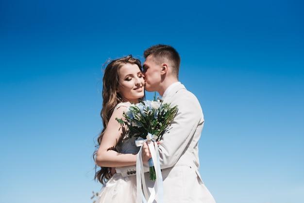 Mariée dans une belle robe étreignant le marié dans un costume léger contre le ciel bleu. histoire d'amour romantique.