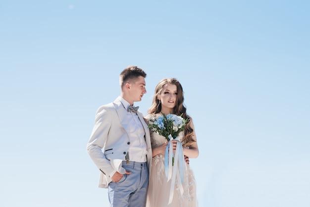 Mariée dans une belle robe étreignant le marié dans un costume léger contre le ciel bleu.