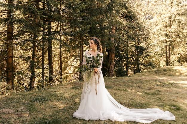 La mariée dans une belle robe longue blanche, tenant un bouquet de mariée