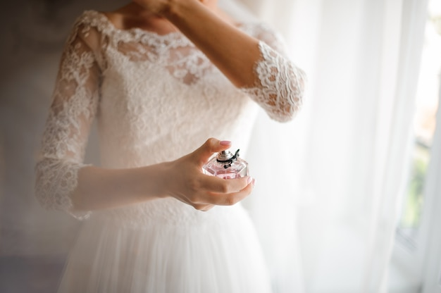 Mariée dans une belle robe de mariée blanche avec un parfum