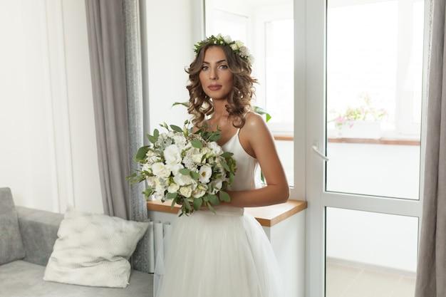 La mariée dans une belle robe de mariée avec de longs cheveux bouclés se tient dans la chambre et regarde la caméra.