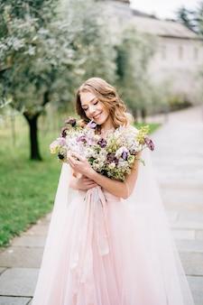 Mariée dans une belle robe rose souriant tient un bouquet de fleurs dans ses mains