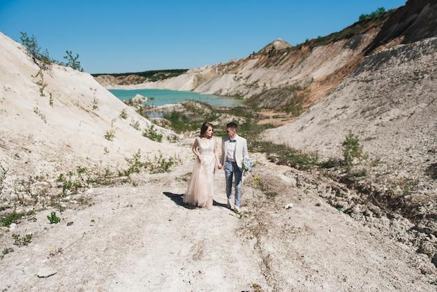 Mariée dans une belle robe tenant la main du marié dans un costume léger contre le ciel bleu et l'eau bleue. couple de mariage debout sur une colline de sable en plein air.