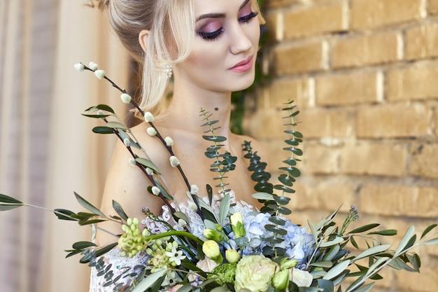 Mariée dans une belle robe turquoise en prévision du mariage. blonde en robe de dentelle vert d'eau avec un bouquet. mariée heureuse, émotion, joie sur son visage. beau maquillage, manucure et coiffures femmes