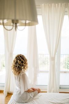 Une mariée dans un doux peignoir assis sur le lit par la grande fenêtre de la terrasse avec des rideaux blancs