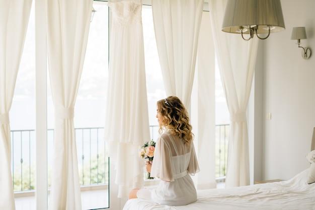 Une mariée dans un doux peignoir avec un bouquet dans ses mains assis près de la fenêtre de la terrasse avec