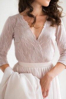 La mariée dans une élégante robe en soie se tient et tient la robe par la ceinture