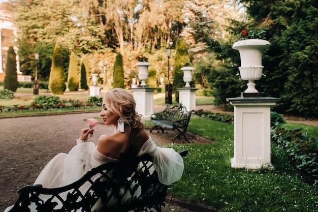 Mariée dans le jardin, mariée assise sur un banc, mariée rassemblant, mariée du matin, robe blanche, mettre des boucles d'oreilles.