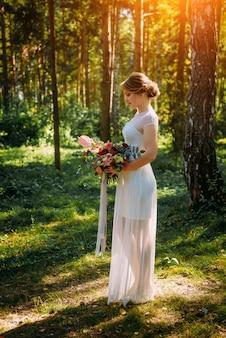 Mariée dans une longue robe blanche dans le parc parmi les arbres