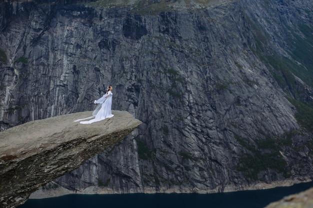 Mariée dans une longue robe de mariée sur un fragment de roche dans les montagnes