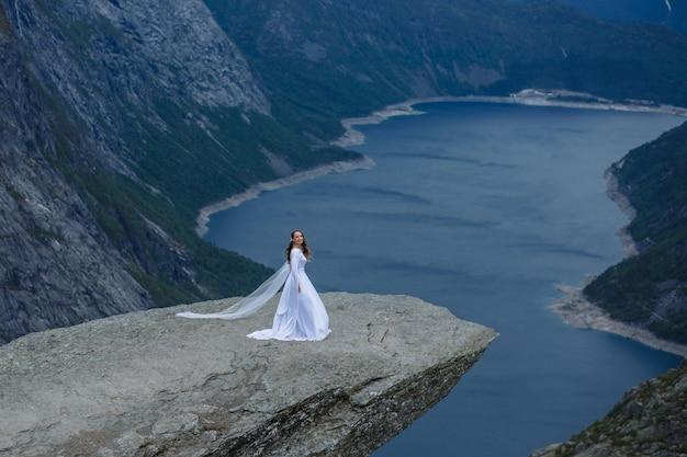 Mariée dans une longue robe de mariée sur un fragment de roche trolltunga dans les montagnes de norvège