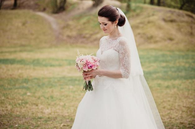 Mariée dans une robe blanche avec un bouquet rose. mariage au printemps