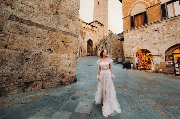 Une mariée dans une robe blanche dans la vieille ville de san gimignano.une fille se promène dans la ville en italie.toscane.
