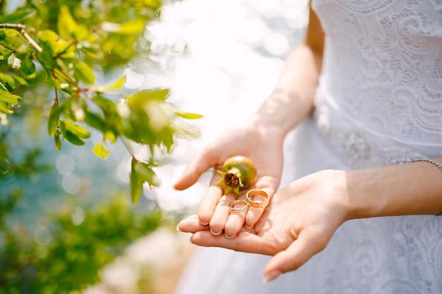 Une mariée dans une robe blanche tient une petite grenade verte et des anneaux de mariage dans ses mains, gros plan.