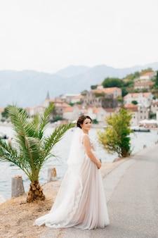 Une mariée dans une robe délicate et un voile se dresse sur la jetée près de la vieille ville de perast