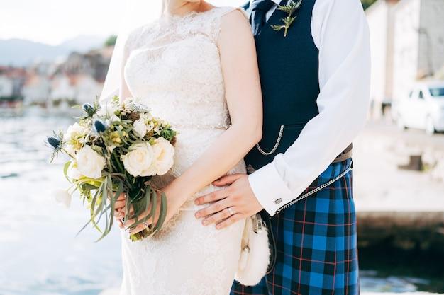 Une mariée dans une robe de mariée avec bouquet de mariée et un marié dans un stand de robe nationale écossaise
