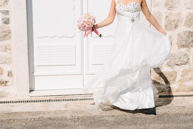Une mariée dans une robe de mariée élégante et avec un bouquet de mariée se tient à la belle porte blanche de