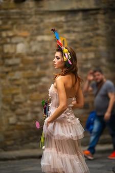 Une mariée dans une robe de mariée rose avec un bouquet et une décoration inhabituelle à gorova à florence