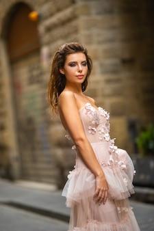 Une mariée dans une robe de mariée rose se promène à florence, en italie.
