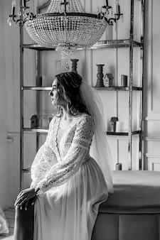 Mariée dans une robe de mariée de style bohème et avec un voile posant assis dans une pièce confortable.