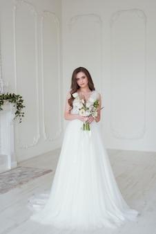 Mariée dans une salle blanche tenant des fleurs