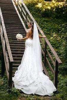 Une mariée dans une très belle robe pose dans les escaliers