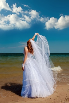 Mariée dans le vent. jolie dame dans une robe de mariée sur la mer