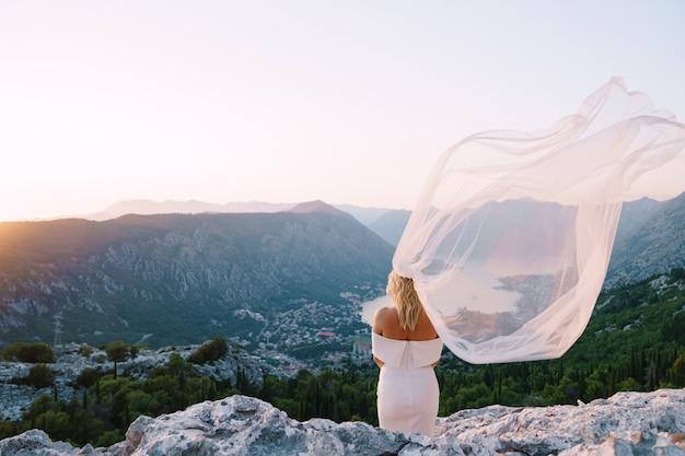 La mariée dans un voile fluide se dresse sur un rocher et donne sur la vue arrière de la baie
