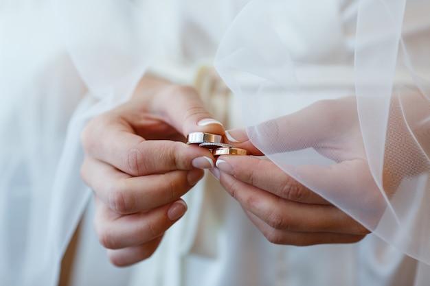 Mariée dans un voile tient dans ses mains trois alliances en or