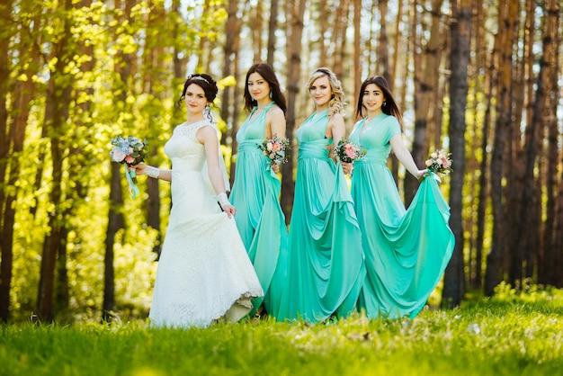 Mariée et demoiselles d'honneur avec des bouquets de mariage. réception de mariage ensoleillée moment joyeux.