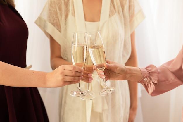 Mariée et demoiselles d'honneur, tinter les verres avec du champagne au jour du mariage